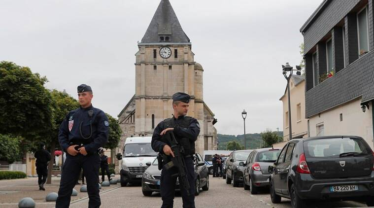 Police officers prevent the access to the church where an hostage taking left a priest dead the day before in Saint-Etienne-du-Rouvray, Normandy, France, Wednesday, July 27, 2016. The Islamic State group crossed a new threshold Tuesday in its war against the West, as two of its followers targeted a church in Normandy, slitting the throat of an elderly priest celebrating Mass and using hostages as human shields before being shot by police. (AP Photo/Francois Mori)