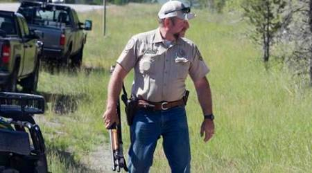 Montana Fish, Wildlife and Parks game warden Perry Brown prepares to hunt for a grizzly bear that killed Forest Service law enforcement officer Brad Treat near West Glacier, Mont. on Wednesday, June 29, 2016.  Treat was off duty-riding his bicycle on a popular trail network near the town when the attack occurred.    (Chris Peterson/The Daily Inter Lake via AP) MANDATORY CREDIT