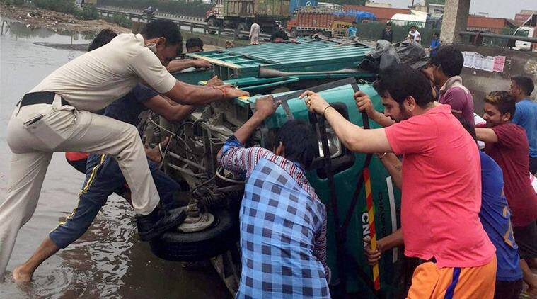 Gurgaon: People trying to upright a vehicle overturned due to a pothole on a road in Gurgaon on Friday. PTI Photo (PTI7_29_2016_000359A)