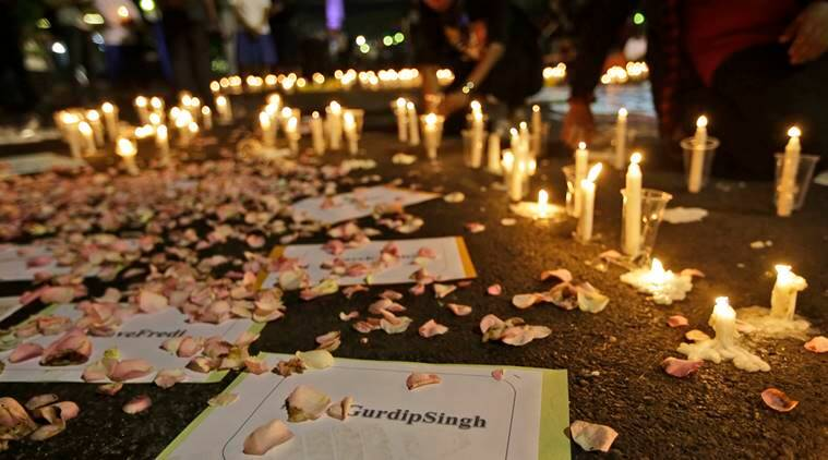 Activists light candles around posters with the names of death row inmates awaiting executions, including that of India national Gurdip Singh, during a vigil against death penalty outside the presidential palace in Jakarta, Indonesia, Thursday, July 28, 2016. Indonesia rebuffed appeals from distraught relatives, rights advocates and foreign governments to abandon plans to execute 14 people for drug crimes as preparations intensified at the prison island holding the inmates. (AP Photo/Dita Alangkara)