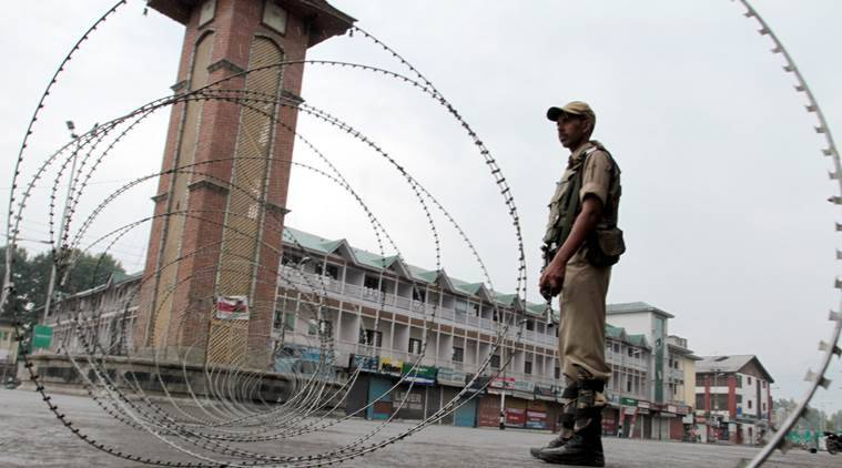 Paramilitary soldier stands guard near a barbed wire setup as barricade during curfew in Srinagar. Express Photo by Shuaib Masoodi 10-06-2016