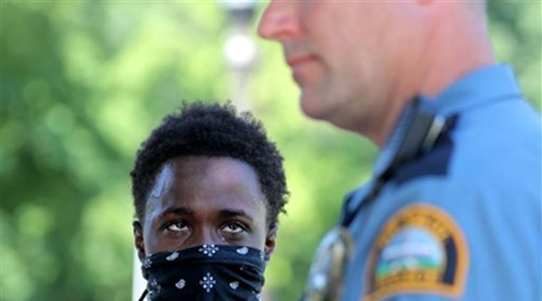 An angry protester stares down a St. Paul police officer after police began making arrests Tuesday, July 26, 2016, in front of Gov. Mark Dayton's mansion, where protesters have been demonstrating over the shooting death of a black man by a suburban police officer nearly three weeks ago, in St. Paul, Minn. (David Joles/Star Tribune via AP)