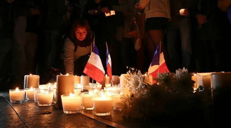 A woman places a candle during a vigil to honor victims of the Bastille Day tragedy in Nice, France, in Sydney, Australia, Friday, July 15, 2016. World leaders are expressing dismay, sadness and solidarity with France over the attack carried out by a man who drove truck into crowds of people celebrating France's national day in Nice. (AP Photo/Rob Griffith)