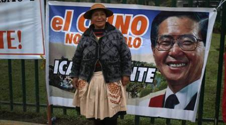 A woman poses for a portrait in front of poster of Peru's jailed, former President Alberto Fujimori during a rally calling for his release in Lima, Peru, Friday, July 22, 2016. Fujimori, who is already serving 25 years following previous convictions, is currently being tried for allegedly diverting government funds to finance newspapers that backed his successful run for a third term. (AP Photo/Martin Mejia)
