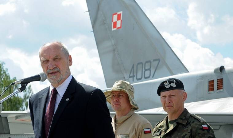 Polish Defense Minister Antoni Macierewicz speaks in front of a Polish Air Force F-16 fighter jet during a farewell ceremony of Polish soldiers leaving for Kuwait to take part in the operation Inherent Resolve , in Janow, Poland, Monday, July 4, 2016. During an interview Monday Macierewicz told The Associated Press that decisions to be approved at this week's NATO summit in Warsaw will build a force aimed at deterring any aggressive intentions by Russia against the West. (AP Photo/Alik Keplicz)