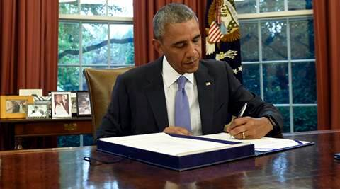 FILE - In this Thursday, June 30, 2016, file photo, U.S. President Barack Obama signs the Puerto Rico Oversight, Management, and Economic Stability Act in the Oval Office of the White House in Washington. Puerto Rico faced a historic default Friday as the U.S. territory prepared to enter unchartered waters under the guidance of a newly enacted federal control board to oversee the island's finances amid a dire economic crisis. Obama approved a rescue package that temporarily protects the territory from lawsuits from creditors who want to recover their investments. (AP Photo/Susan Walsh, File)