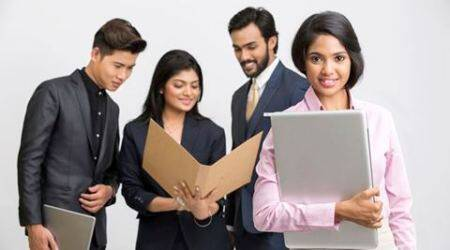 Proud businesswoman holding laptop with her colleagues on white background