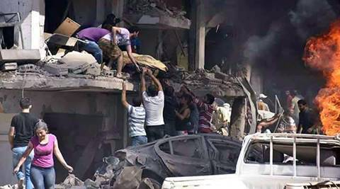In this photo released by the Syrian official news agency SANA, Syrians carry the body of a victim from a building damaged in twin bombings struck Kurdish town of Qamishli, Syria, Wednesday, July 27, 2016. Bombings struck a crowd in a predominantly Kurdish town in northern Syria on Wednesday, killing 44 people and wounding dozens more, Syria's state-run news agency and Kurdish media reported. (SANA via AP)