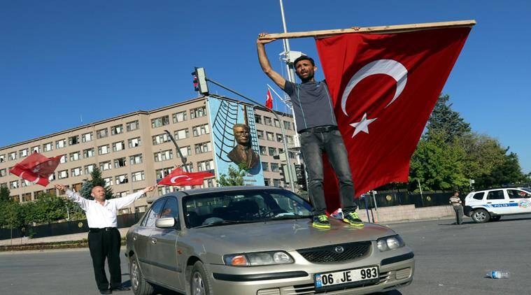 A man waves a Turkish flag as people protest against a coup near the Turkish military headquarters, in Ankara, Turkey, Saturday, July 16, 2016. (AP Photo/Ali Unal)