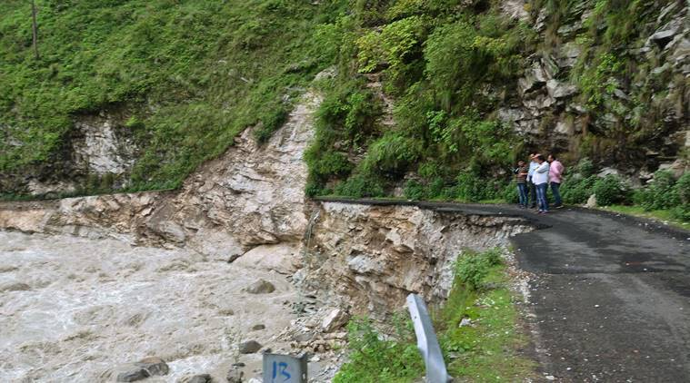 Chamoli : People look on a damaged road affected by cloudbursts in Chamoli and Pithoragarh districts of Uttarakhand on Sunday. PTI Photo (PTI7_3_2016_000196A)