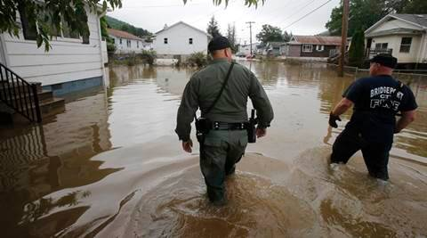 FILE - In this June 25, 2016, file photo, West Virginia State Trooper C.S. Hartman, left, and Bridgeport W. Va., fireman, Ryan Moran, wade through flooded streets as they search homes in Rainelle. A rainstorm that seemed no big deal at first turned into a catastrophe for the small town in West Virginia, trapping dozens of people whose screams would echo all night. (AP Photo/Steve Helber, File)