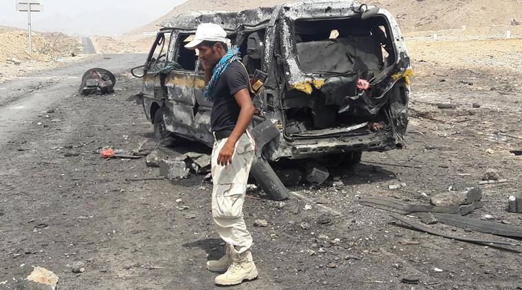 A soldier talks on a mobile phone as he stands at the site of a suicide car bomb attack at a military checkpoint near the government-held port city of Mukalla, Yemen. (Reuters)