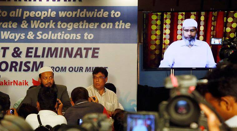 Indian journalists listen to a video conference of controversial Islamic preacher and the founder of Islamic Research Foundation, Zakir Naik, right, in Mumbai, India, Friday, July 15, 2016. Naik, who is presently out of the country, faced a lot of criticism as it came to be known that a few of the attackers of Holey Artisan Bakery in Bangladesh were influenced by his preachings. (AP Photo/ Rajanish Kakade )