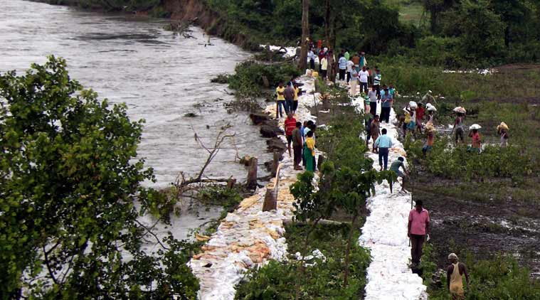 Villagers repairing the embankment of a river voluntarily to protect their villages from flood water at Narayanguri near Manas National Park in Baksa district of Assam on Thursday. (Source: PTI)