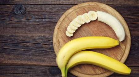 Ripe bananas and a sliced on wooden cutting board, top view