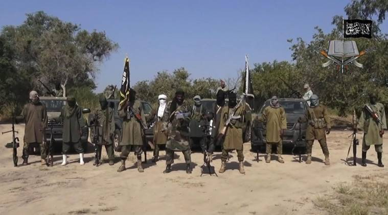 "FILE - In his file image taken from video released late Friday evening, Oct. 31, 2014, by Boko Haram, Abubakar Shekau, centre, the leader of Nigeria's Islamic extremist speaks in an unidentified place. Boko Haram leader Abubakar Shekau is believed to be fatally wounded in an airstrike while he was praying in a forest stronghold in northeast Nigeria, the military said Tuesday Aug. 23, 2016 A statement does not say how the military got the information but it identifies other commanders as ""confirmed dead.""(AP Photo/Boko Haram,File)"
