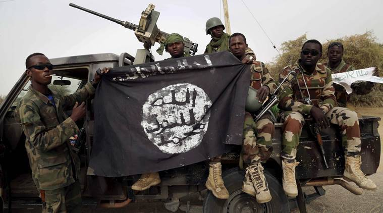 Nigerian soldiers hold up a Boko Haram flag that they had seized in the recently retaken town of Damasak, Nigeria, March 18, 2015. REUTERS/Emmanuel Braun/File Photo