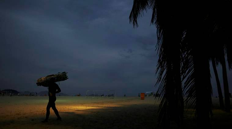 A man carries chairs to be rented to visitors on Copacabana beach