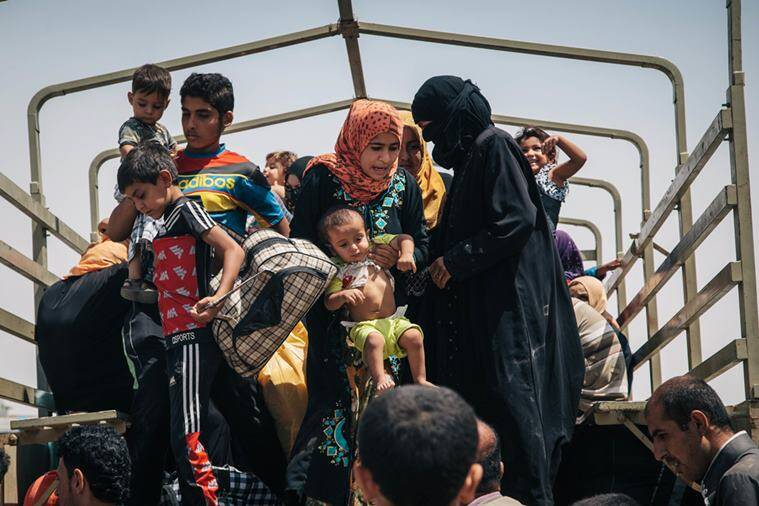 In this Aug. 17, 2016 photo, civilians who recently fled territory formerly controlled by Islamic State militants get off a truck at the Dibaga Camp for displaced people in Hajj Ali, northern Iraq. As the Islamic State group loses ground in Iraq, the militants are showing strains in their rule over areas they still control, growing more brutal, killing deserters and relying on younger recruits, according to residents. The accounts pointed to the difficulties the extremist group is facing as Iraqi forces backed by the United States prepare for an assault on Mosul. (AP Photo/Alice Martins)