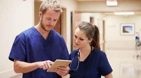 Medical Staff Looking At Digital Tablet In Hospital Corridor
