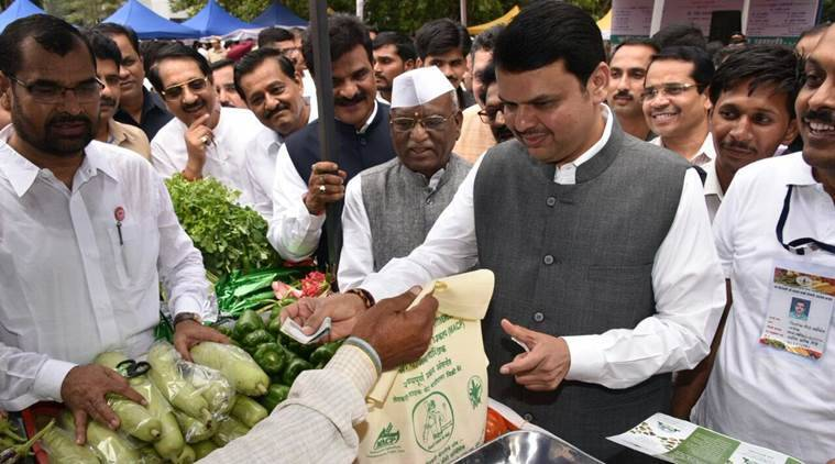 "Chief Minister Devendra Fadnavis buying fresh farm vegetables at a ""Shetkari Bazaar""  to promote farmers vegetables and fruits. The CM inaugurated Sant Shri Savta Mal Farmer Market (ShetkariBaazar) at Vidhan Bhawan premises in Mumbai. CM also paid the money for the vegetables to the farmers. (Express Photo by Shubhangi Khapre)"