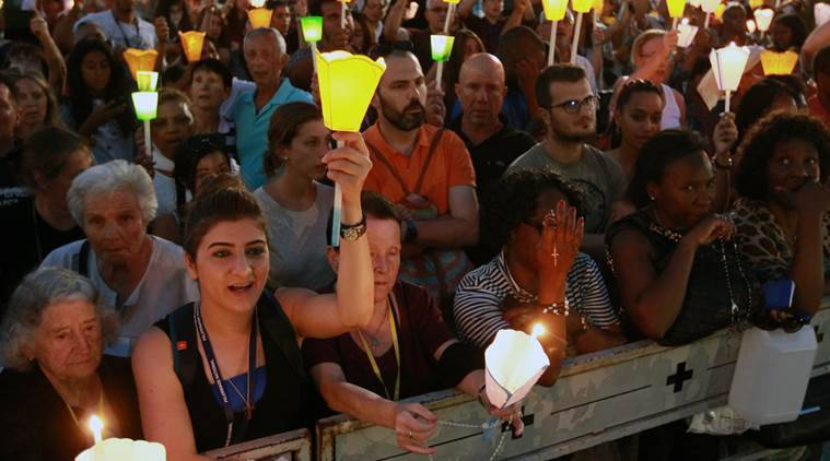 Pilgrims attend a candlelight procession for the Virgin Mary at the sanctuary of Lourdes, southwestern France, Sunday, Aug. 14, 2016. (AP Photo/Bob Edme)