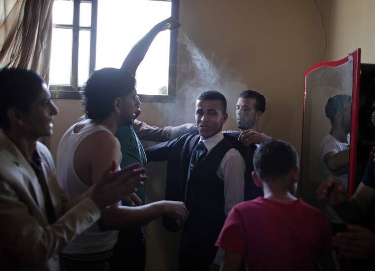 In this Saturday, July 30, 2016 photo, friends of Palestinian groom Saed Abu Aser, spray him with cologne as they help him get dressed for his wedding, at the family house in Gaza City. Weddings have emerged as a welcome celebration that slices through the often morose mood in the Gaza Strip, a Palestinian coastal territory run by the militant group Hamas. For both poor and well-off Gazans, weddings are a days-long, lavish affair of parties and dancing. (AP Photo/ Khalil Hamra)