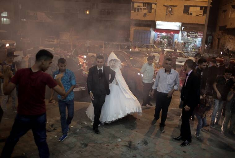In this Saturday, July 31, 2016 photo, Palestinian groom Saed Abu Aser, and his pride, Falasteen, walk into the wedding hall amid smoke from fireworks, in Gaza City. Weddings in Gaza have emerged as a welcome celebration that slices through the often morose existence in the Gaza Strip. The coastal territory has been beaten down by three wars with Israel over the last decade and a stifling blockade imposed by Israel and Egypt. (AP Photo/ Khalil Hamra)