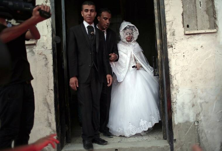In this Saturday, July 30, 2016 photo, Palestinian groom Saed Abu Aser, 22, walks with his bride, Falasteen, out of her family house to the wedding hall to celebrate their wedding, in Gaza City. Weddings have emerged as a welcome celebration that slices through the often morose mood in the Gaza Strip, a Palestinian coastal territory run by the militant group Hamas. For both poor and well-off Gazans, weddings are a days-long, lavish affair of parties and dancing. (AP Photo/ Khalil Hamra)