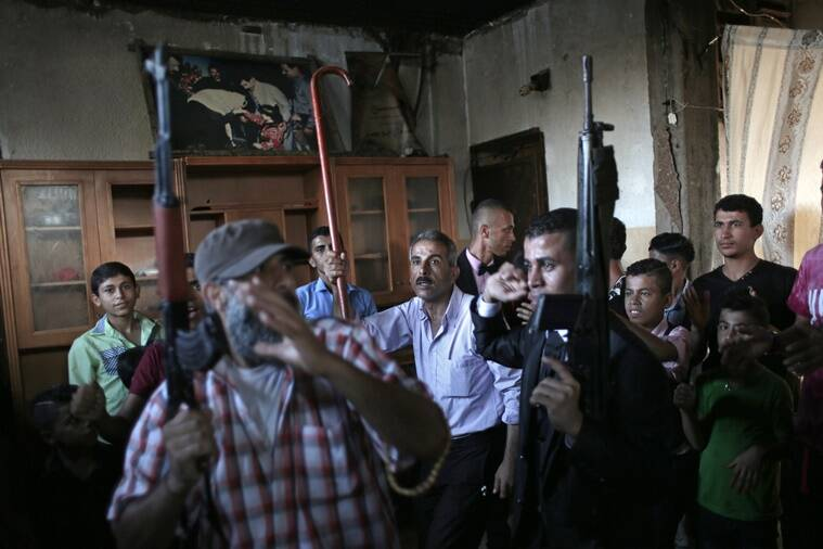 In this Saturday, July 30, 2016 photo, Palestinian groom Saed Abu Aser, center right, dances with relatives while holding guns in the family house during his wedding party, in Gaza City. Weddings have emerged as a welcome celebration that slices through the often morose mood in the Gaza Strip, a Palestinian coastal territory run by the militant group Hamas. For both poor and well-off Gazans, weddings are a days-long, lavish affair of parties and dancing. (AP Photo/ Khalil Hamra)