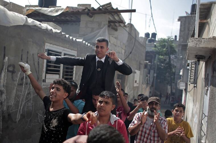 In this Saturday, July 30, 2016 photo, friends and relatives of Palestinian groom Saed Abu Aser, dance in the streets around the neighborhood, while being carried on a friend's shoulders, before his wedding party, in Gaza City. Weddings have emerged as a welcome celebration that slices through the often morose mood in the Gaza Strip, a Palestinian coastal territory run by the militant group Hamas. For both poor and well-off Gazans, weddings are a days-long, lavish affair of parties and dancing. (AP Photo/ Khalil Hamra)