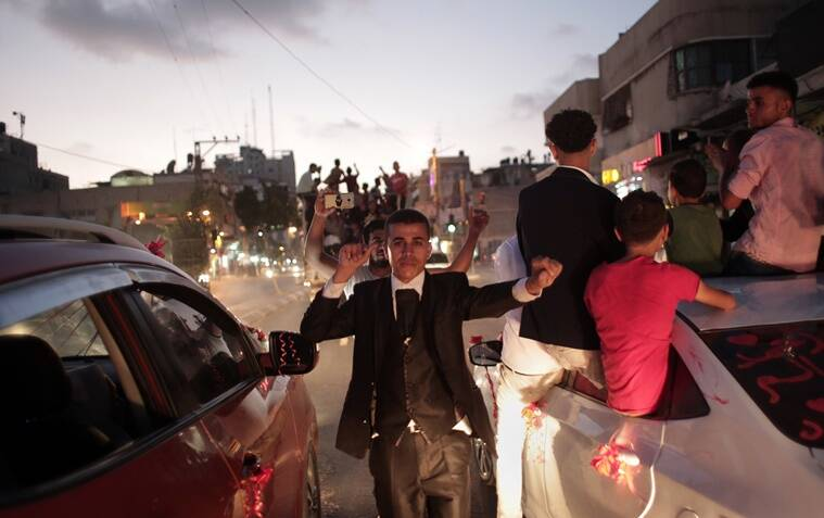 In this Saturday, July 30, 2016 photo, Palestinian groom Saed Abu Aser, dances in the street on his way to the wedding hall, in Gaza City. Weddings have emerged as a welcome celebration that slices through the often morose mood in the Gaza Strip, a Palestinian coastal territory run by the militant group Hamas. For both poor and well-off Gazans, weddings are a days-long, lavish affair of parties and dancing. (AP Photo/ Khalil Hamra)