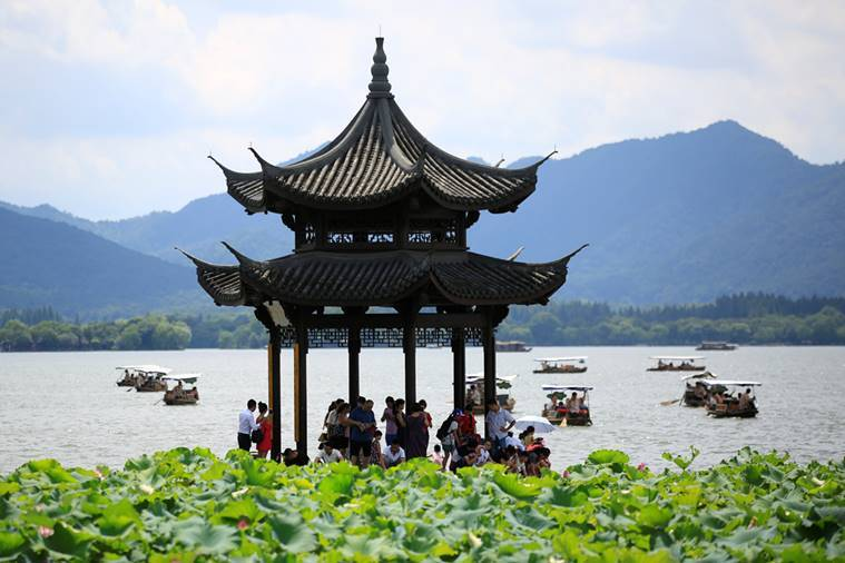 Visitors take shelter from the sun under a pavilion as they visit the West Lake in Hangzhou, Zhejiang province, China, August 3, 2016. REUTERS/Aly Song