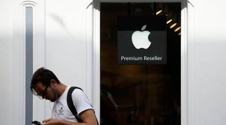 A man looks at his phone as he walks past an authorised apple reseller store in Galway, Ireland August 30, 2016. REUTERS/Clodagh Kilcoyne