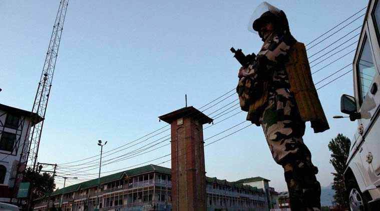 A security jawan stands guard during night curfew in Lal Chowk area of Srinagar on Sunday. (PTI Photo)