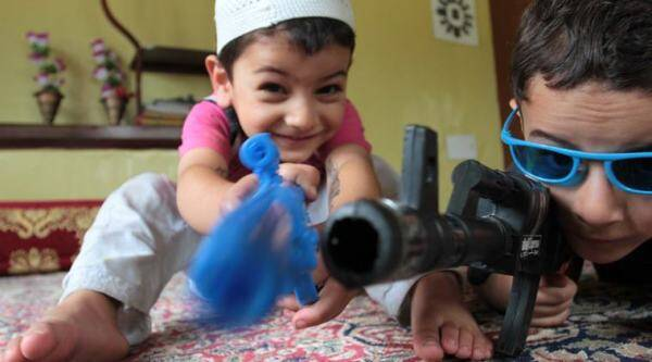 Kashmiri children simulating like militants with toy guns in their homes.Acting as militants in daily indoor home plays is a common engagment among Kashmiri Children. (Express Photo by Shuaib Masoodi)