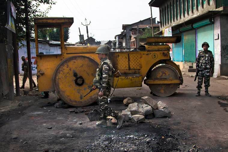 Indian paramilitary soldiers stand guard near a road roller used as road block by protesters during earlier protests as curfew continues in Srinagar, Indian controlled Kashmir, Wednesday, Aug. 17, 2016. Curfew and protests have continued across the valley amidst outrage over the killing of a top rebel leader by Indian troops in early July, 2016. (AP Photo/Dar Yasin)