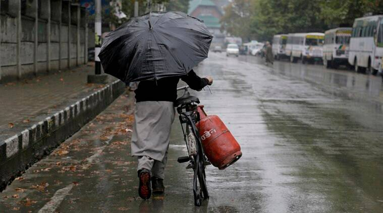 A Kashmiri man pushes his bicycle carrying cooking gas cylinder as it rains in Srinagar, Indian controlled Kashmir, Sunday, Aug. 28, 2016. A strict curfew, a series of communication blackouts and a tightening crackdown have failed to stop some of Kashmir's largest protests against Indian rule in recent years, triggered by the killing of a popular rebel commander on July 8. (AP Photo/Mukhtar Khan)