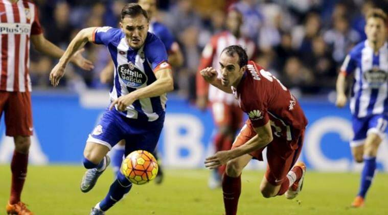 Deportivo Coruna's Lucas fights for the ball with Atletico Madrid's Godin during their Spanish First Division soccer match at Riazor stadium in Coruna, Spain