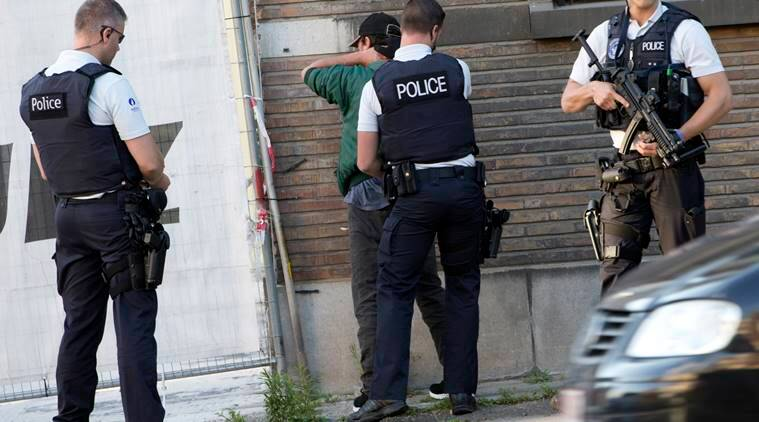 """Police officers check the identification of a man near the police headquarters in Charleroi, Belgium on Saturday, Aug. 6, 2016. Ôªø Two female officers were attacked and wounded by a man wielding a machete and shouting """"Allahu Akhbar"""" outside a police station in the Belgian city of Charleroi on Saturday, police said. (AP Photo/Virginia Mayo)"""