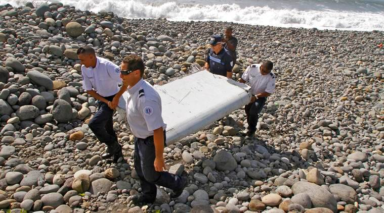 FILE - In this July 29, 2015, file photo, French police officers carry a piece of debris, the first trace of Malaysia Airlines Flight 370, in Saint-Andre, Reunion Island. With the Friday, July 22, 2016, announcement that the meticulous ocean search operations for missing Malaysia Airlines Flight 370 would be suspended, the epic arc of one of this decade's most vexing unanswered questions is headed toward becoming, in effect, a cold case. (AP Photo/Lucas Marie, File)