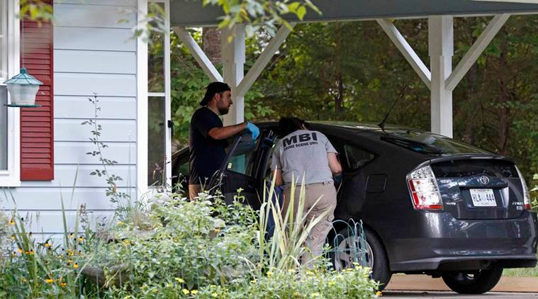 Two Mississippi Bureau of Investigation agents inspect a car in the garage of the Durant, Miss., home of two slain Catholic nuns who worked as nurses at the Lexington Medical Clinic, Thursday, Aug. 25, 2016. The clinic office manager and a Durant police officer discovered their bodies inside the house after both nuns did not report for work. Authorities said their were signs of a break-in and their vehicle was missing. (AP Photo/Rogelio V. Solis)