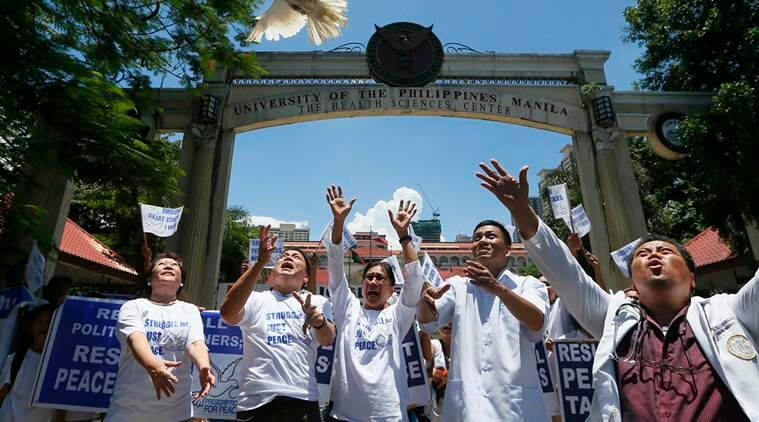 Community health workers release white doves following a protest-motorcade around Manila to call for the resumption of the peace talks between the Government and communist rebels Wednesday, Aug. 3, 2016, in Manila, Philippines. (AP Photo/Bullit Marquez)