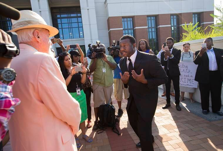 Earl Lewis, cousin of William Chapman II, right, gestures during a heated discussion with Bill Garrett with the Chesapeake Citizens Police Academy Alumni Association in front of the Portsmouth Judicial Center Wednesday morning, July 27, 2016, Portsmouth, Va. Wednesday is the first day of trial for ex-Portsmouth police officer Stephen Rankin who is charged with first degree murder in the shooting death of William Chapman II last year in a Wal-Mart parking lot in Portsmouth. (Bill Tiernan/The Virginian-Pilot via AP)