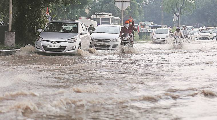 Commuters crossing flooded road near housing board lightpoint in Manimajra  due to heavy rain on Thursday in Chandigarh,  August 04 2016. Express Photo by Kamleshwar Singh