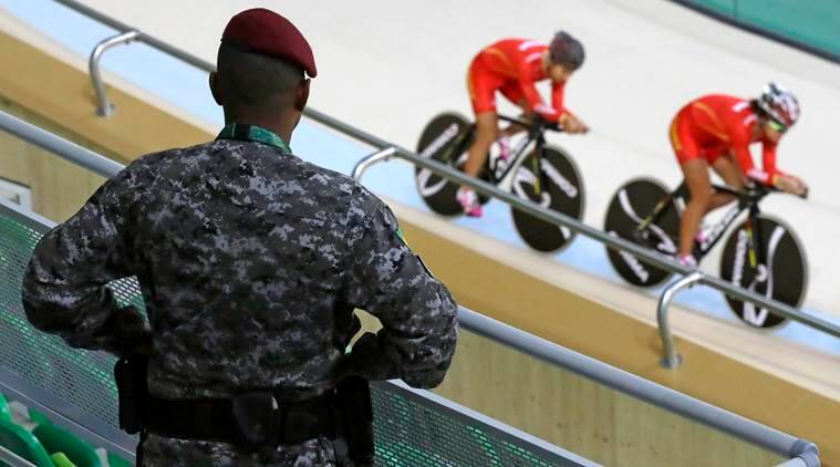 A police officer watches as members of the Chinese women's track cycling team round the track during a training session inside the Rio Olympic Velodrome in advance of the 2016 Olympic Games in Rio de Janeiro, Brazil, Thursday, Aug. 4, 2016. (AP Photo/Patrick Semansky)