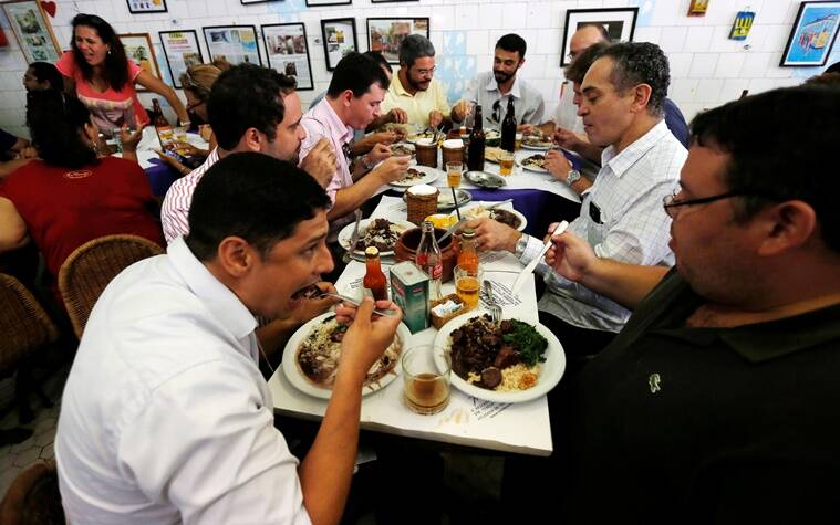 "People enjoy the Brazilian traditional dish called feijoada (black bean and meat stew) at the Bar do Mineiro in Rio de Janeiro, Brazil, March 24, 2016. REUTERS/Sergio Moraes SEARCH ""RIO FOOD"" FOR THIS STORY. SEARCH ""THE WIDER IMAGE"" FOR ALL STORIES."