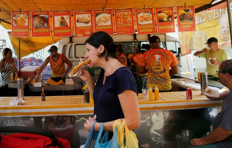 """A woman eats a street market purchased pastel de feira (pastry) in Rio de Janeiro, Brazil, May 7, 2016. REUTERS/Sergio Moraes SEARCH """"RIO FOOD"""" FOR THIS STORY. SEARCH """"THE WIDER IMAGE"""" FOR ALL STORIES."""