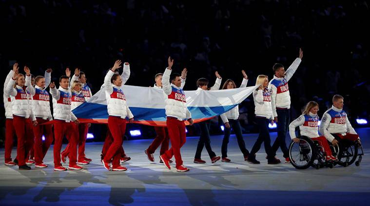 Performers carry Russian national flag during closing ceremony of 2014 Paralympic Winter Games in Sochi
