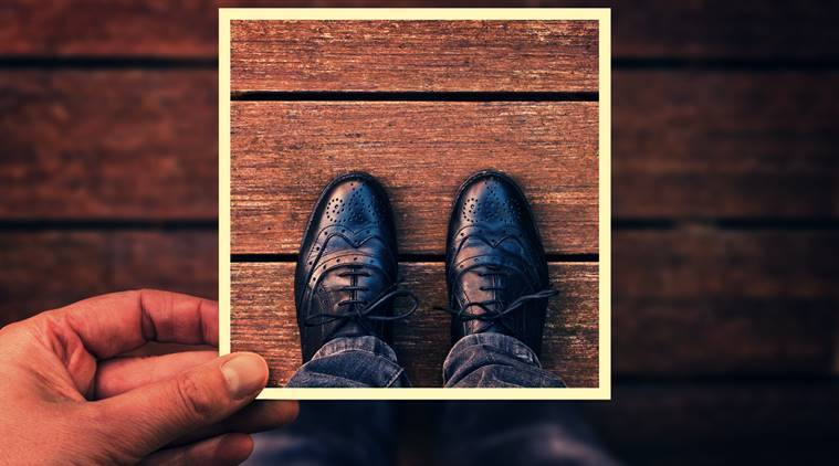 Selfie of foot and legs with black derby shoes seen from above with hand holding an instant photo frame, vintage process
